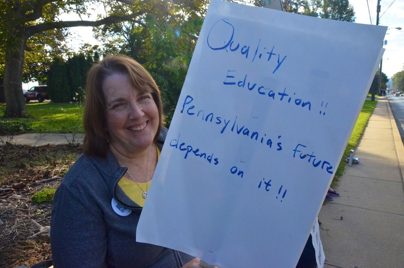 """Dr. Kirsten Bookmiller Holds Sign That Says, """"Quality Education is the Key to PA Future"""""""