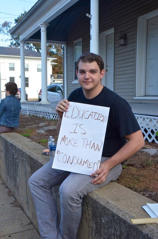 """Student Protester Holds Sign That Says: Education is more than """"Consumed"""""""